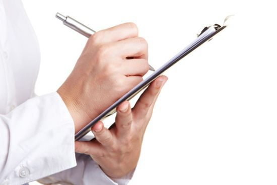 Hand filling out checklist on clipboard